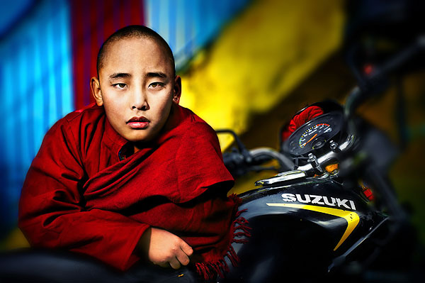 The-boy-monk-in-red-robe-standing-beside-a-motorcycle-in-a-Buddhist-monastery-in-Kathmandu-Nepal