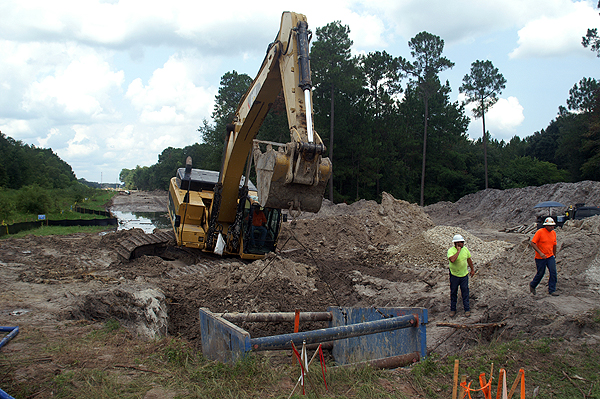 Excavator moving a trench box
