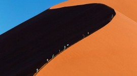 Tourists-climbing-a-red-dune-at-Namib-Naukluft-National-PArk-Namibia